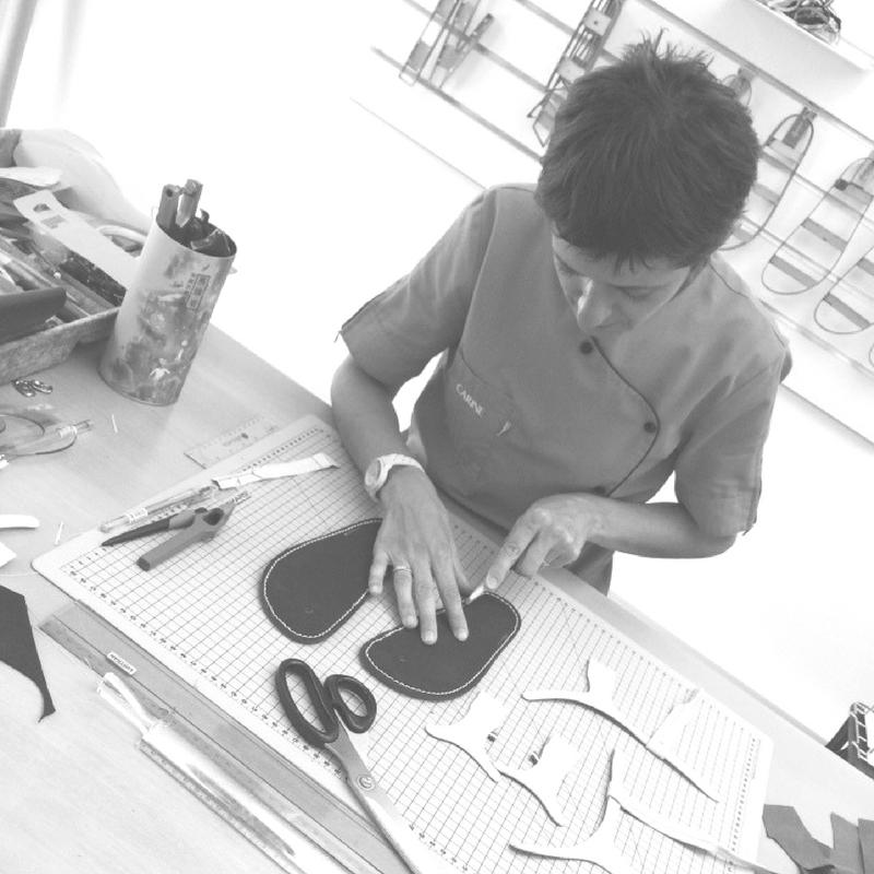 Cette photo représente Carine Begouin Cariou en train de découper du cuir pour faire une paire de sandales sur-mesure